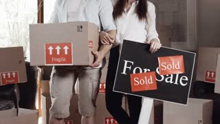 Young couple portrait with there boxes and for sale/sold sign board and there new apartment/ house while moving in.