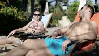 Young couple relaxing on sunbed and talking