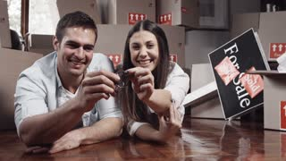 Young couple smile with happiness with new house keys for their new apartment.