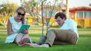 Young couple spending free time on the green lawn.  Woman using a touchpad, man reading a book