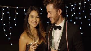 Young couple toasting the New Year with champagne smiling with joy as they clink glasses against strings of twinkling party lights