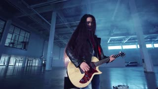 Young emotional expressive asian musician woman in black leather jacket playing the electric guitar in hangar