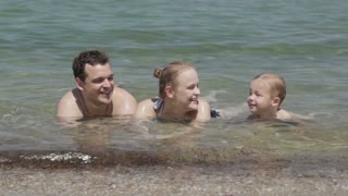 Young family splashing in the sea with their small son lying in the shallow surf in the summer sun