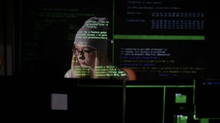 Young female in dark inputting data, computer codes, breaking security system