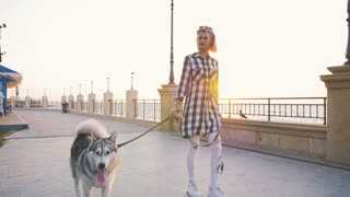 Young female walking with siberian husky dog on sea front, slow motion