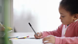 Young girl colouring in with coloured pens