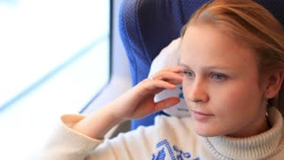 Young girl is travelling by a high-speed train.