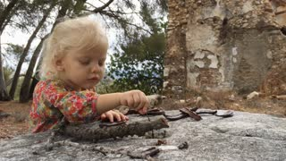 Young girl playing with sticks by old buildings