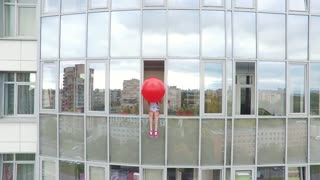 Young Girl With A Red Balloon Sits On The Window