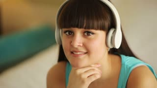 Young girl with headphones smiling at camera