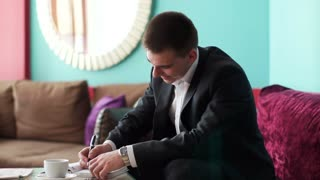 Young guy sitting in cafe and writing in a notebook