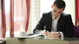 Young guy writing and laughing at camera