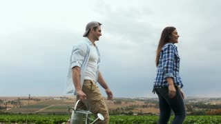Young happy lifestyle farming couple carrying water can and inspecting produce before harvest.