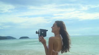 Young happy woman having fun with old film camera at the summer beach holidays