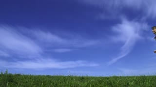 Young happy woman is running and jumping by the camera. Blue sky and green grass on the background. Slow motion 240 fps. Freedom and happiness concept.