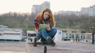 Young happy woman with red hair curls sitting and drawing with pen at the seacoast