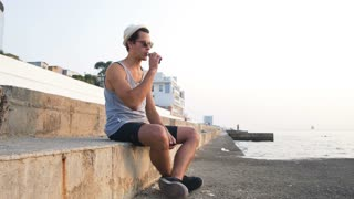 Young hipster man vaping on sea front