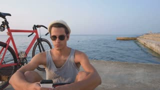 Young hipster man with his fixed gear bike using smart phone near the sea, slow motion