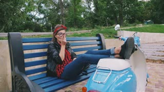 Young hipster woman in glasses sitting on a bench and smoking cigarette, slow mo