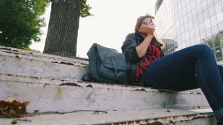Young hipster woman in glasses sitting on stairs and smoking cigarette, slow motion