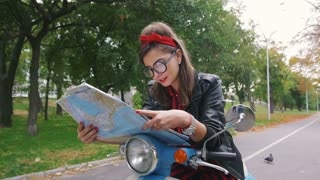 Young hipster woman sitting on a vintage scooter with map in park