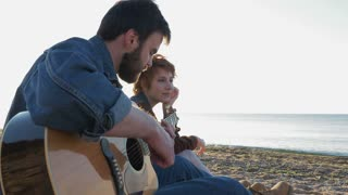 Young loving couple playing guitar on the beach, 4k