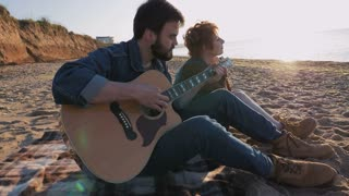 Young loving couple playing guitar on the beach