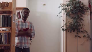Young man African-American student in glasses wearing checked shirt walking through library while reading book, following camera. Low angle shot