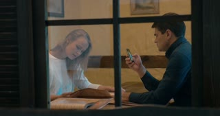 Young man and woman in cafe or restaurant. They looking through the menu, man using smart phone while choosing a dish. View through the latticed window