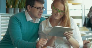 Young man  and woman in glasses sitting in cafe and using tablet computer. They surfing the Internet to find something and discussing it. Business time