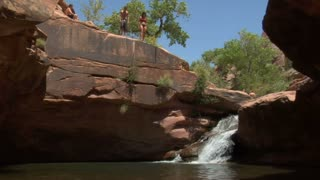 Young Man And Woman Jump Off Red Rock Cliffs Into Water