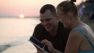 Young man and woman on the beach at sunset looking through the photos on touch pad, talking and laughing
