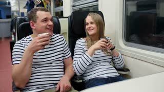 Young man and woman talking and drinking tea or coffee while traveling by train in the evening