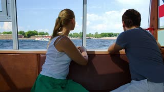 Young man and woman traveling by tourist boat on river. They enjoying panorama and talking