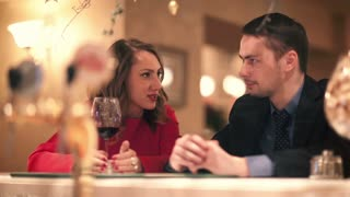 Young man and woman with a glass of wine talking while sitting at the bar counter