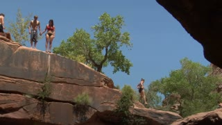Young Man And Women Jump Off Red Rock Cliffs Into Water