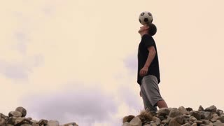 Young Man Balancing Soccer Ball on Head