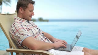 Young man chatting with laptop by swimming-pool in hotel, steadicam