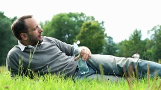 Young man drinking water while lying on grass in the park