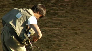 Young Man Fly Fishing Catches And Releases Large Trout