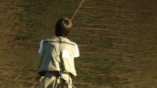 Young Man Fly Fishing Catches Trout