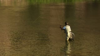 Young Man Flyfishing With Fish On Line