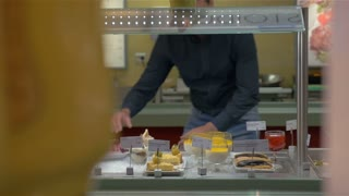 Young man is taking bakery from the counter in self-service buffet.