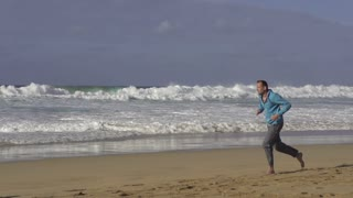 Young man jogging on the seashore, slow motion shot at 240fps
