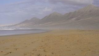 Young man jogging on the seashore, slow motion shot at 60fps
