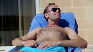 Young man lying on sunbed and applying sun cream