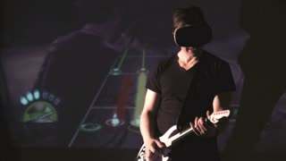 Young man playing in musical virtual game using VR helmet with head mount display