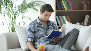 Young man relaxing on sofa reading book and drinking juice