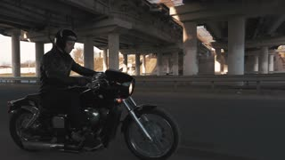 Young man riding motorcycle on the road under the bridge at sunset, slow motion
