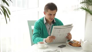 Young man sitting at table reading newspaper drinking tea and smiling. Panning camera